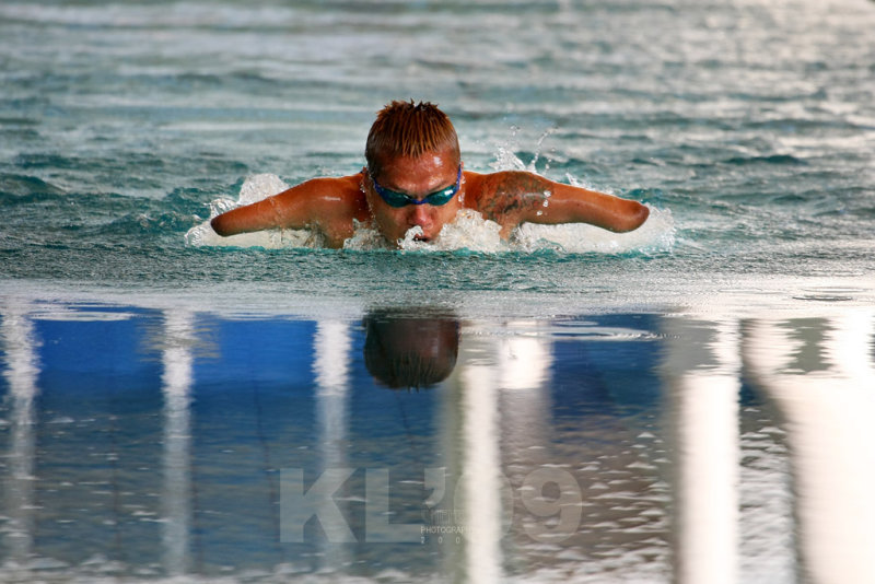 KUALA LUMPUR - AUGUST 18: Triple amputee swimmer Doungkaew Somchai from Thailand propers himself in the pool on one leg at the K