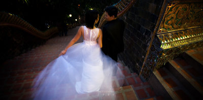A wedding couple making their way down the steps