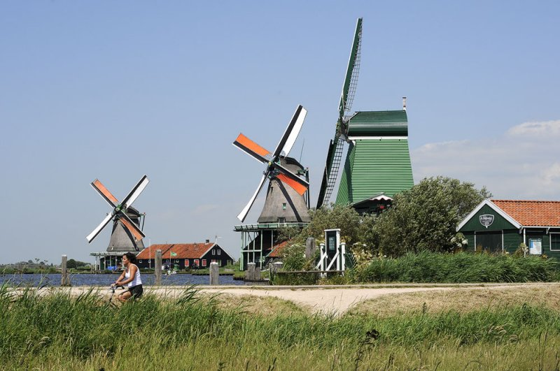 3 windmills, a river and a cyclist