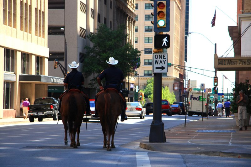 TWO COPS, TWO HORSES, TWO COWBOY HATS WALKING DOWNTOWN FORT WORTH