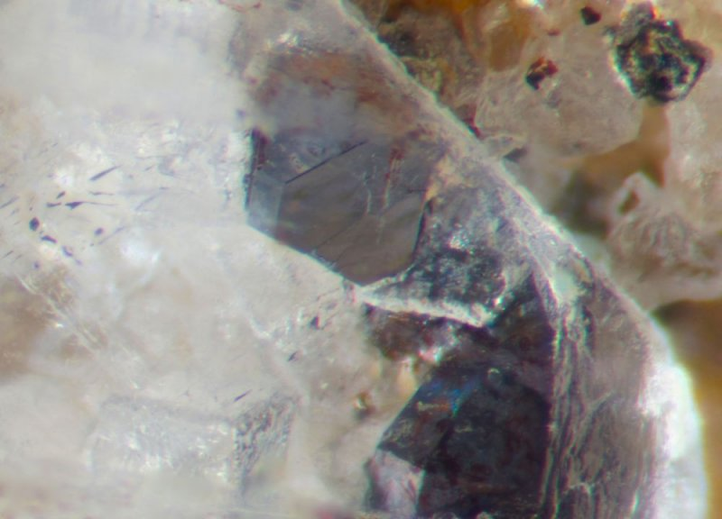 Pristine galena cuboctahedra and a colourless fluorite cube seen through the window of a 5 mm Wetgrooves barite crystal.