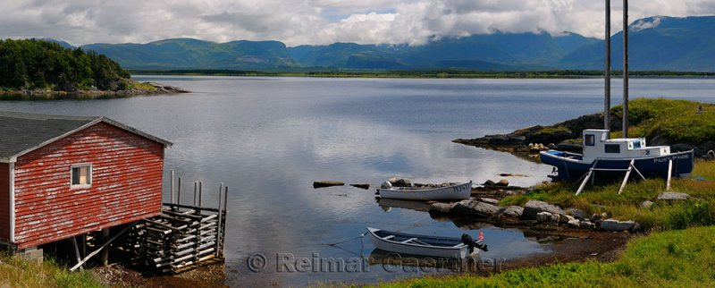 Panorama of boathouse and boats at St Pauls Inlet Newfoundland with Gros Morne Long Range Mountains