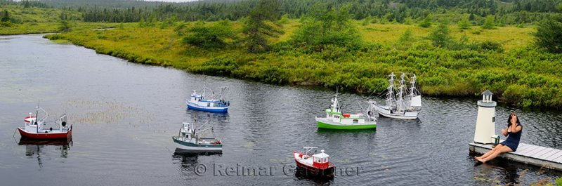 Panorama of model ships and lighthouse with girl on dock of river between Mobile and Witless Bay Newfoundland