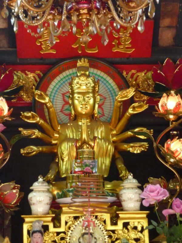 Close-up of the golden multi-armed Buddha inside of the pagoda.