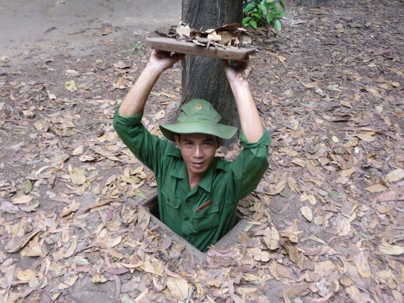 This guide, who was dressed up like a Vietcong soldier, was demonstrating an entrance to the tunnels.