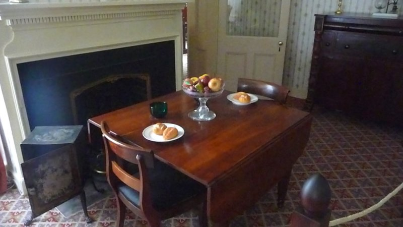 The table is set with a simple breakfast of bread and fruit.