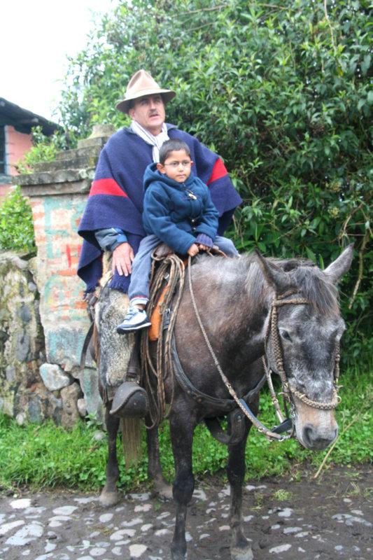 A cowboy with his son on horseback at the hacienda.