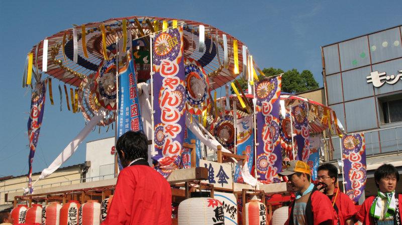 Ornamented umbrellas atop the floats