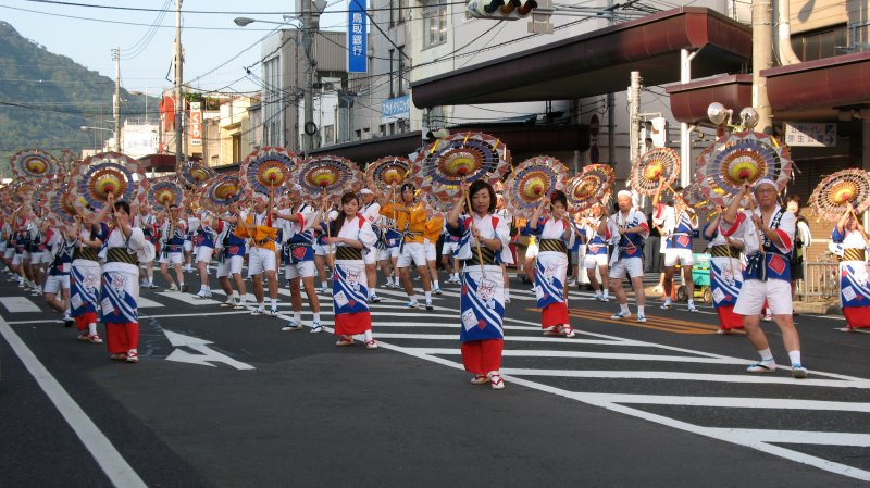 Group of Shan Shan dancers coming down the road