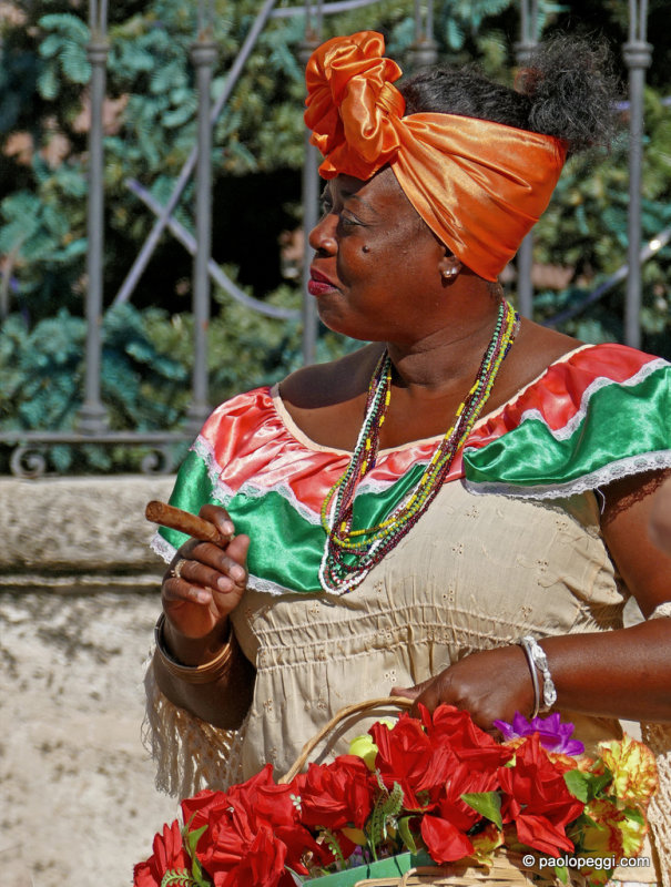 Lady in traditional garb smoking a Cuba cigar,  Havana, Cuba