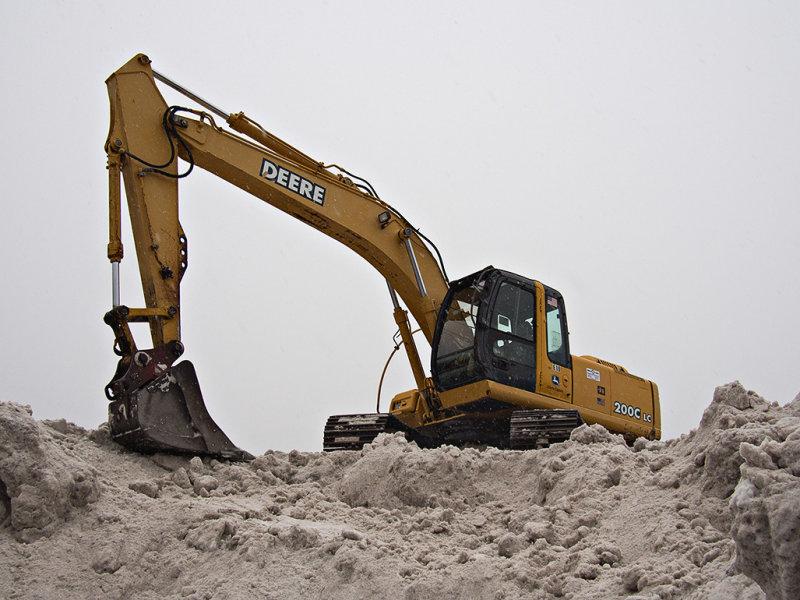 Excavator on snow pile #2