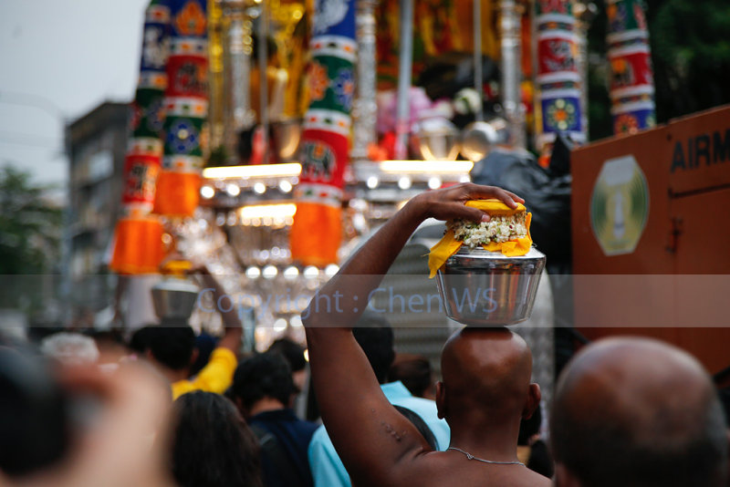 Devotees walking alongside the chariot bearing Lord Muruga