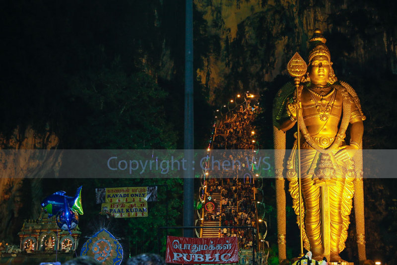 Lord Muruga watches over. Kavadi carriers can be seen climbing up the steps to the cave temple