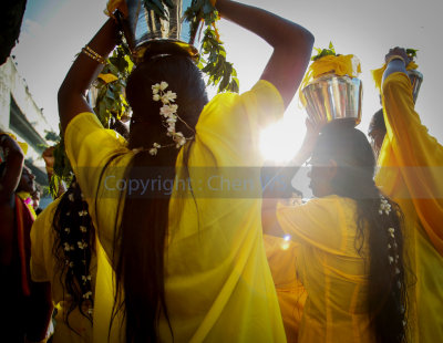 Devotees with milk pots on the head walks to the cave temple