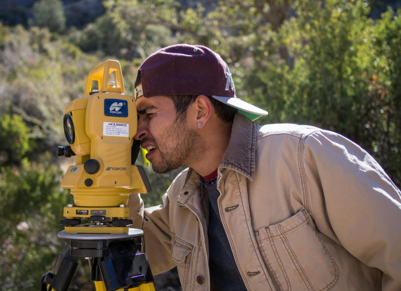 Angel Pena using a total station