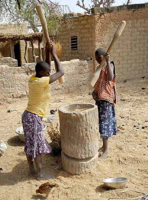 Girls threshing millet by pounding the grains, Burkina Faso