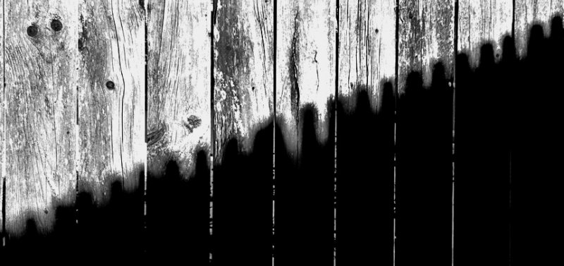 Picket shadow on a fence