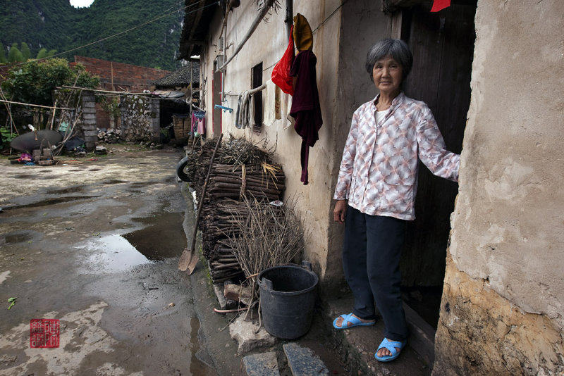 Farm lady outside her house in a village in Xing Ping.