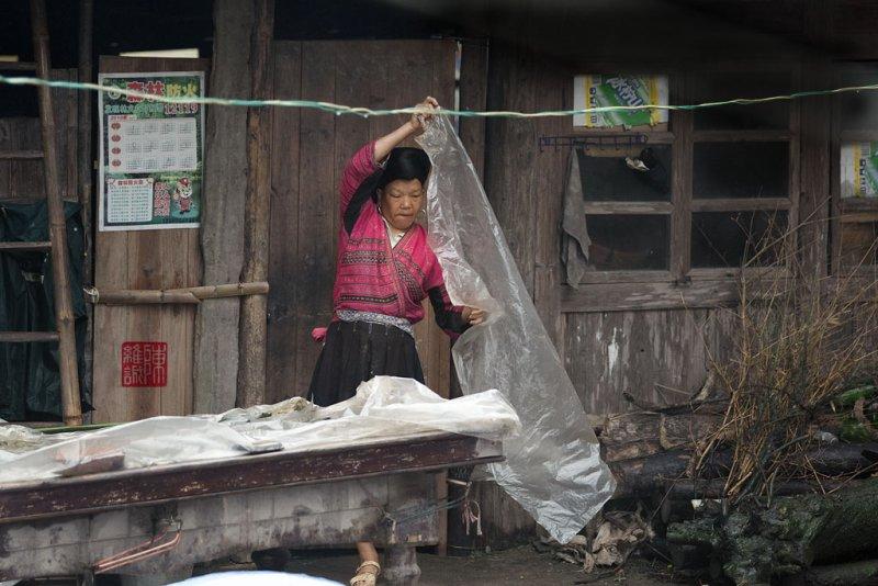Putting on a rain cover, DaXai village, Long Ji, China