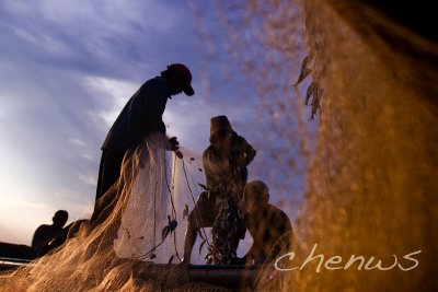 BALI, INDONESIA - JANUARY 16: Fishermen continue to work at dusk, removing their days catch from the fishing nets on January 16