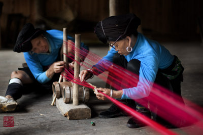GUANGXI, CHINA - MAY 21: Womenfolk from the Yao ethnic minority weave garments the traditional method at their homes on May 21,