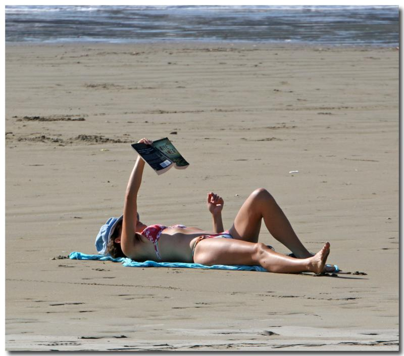Relaxing And Reading A Book On The Beach