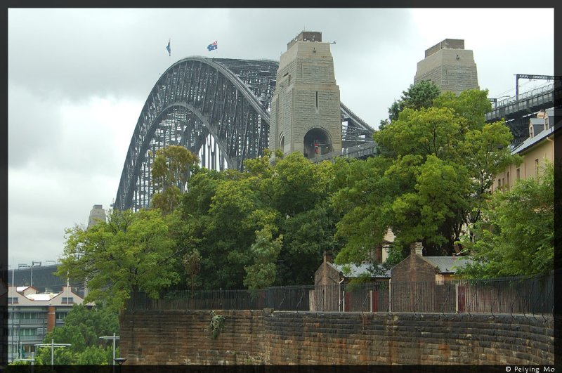 On a rainy and overcast day, the Harbour Bridge rises above Sydneys Rocks district