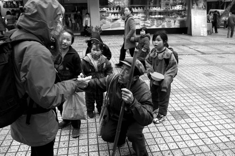 Begging in the street and training his children.