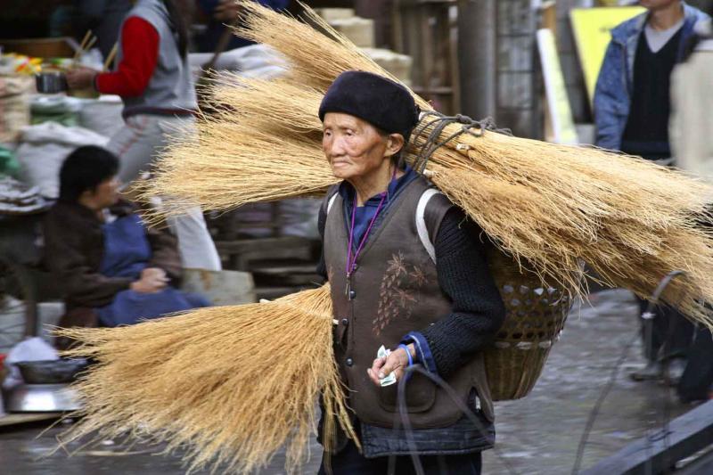 Elderly woman taking brooms to market. Jishou City, China.