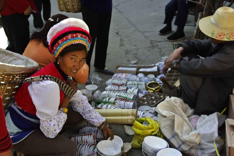 Bai woman in market place purchasing bowls Dali China .jpg