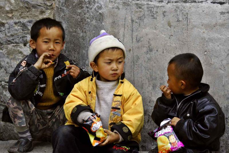 Three boys eating chips Dali China