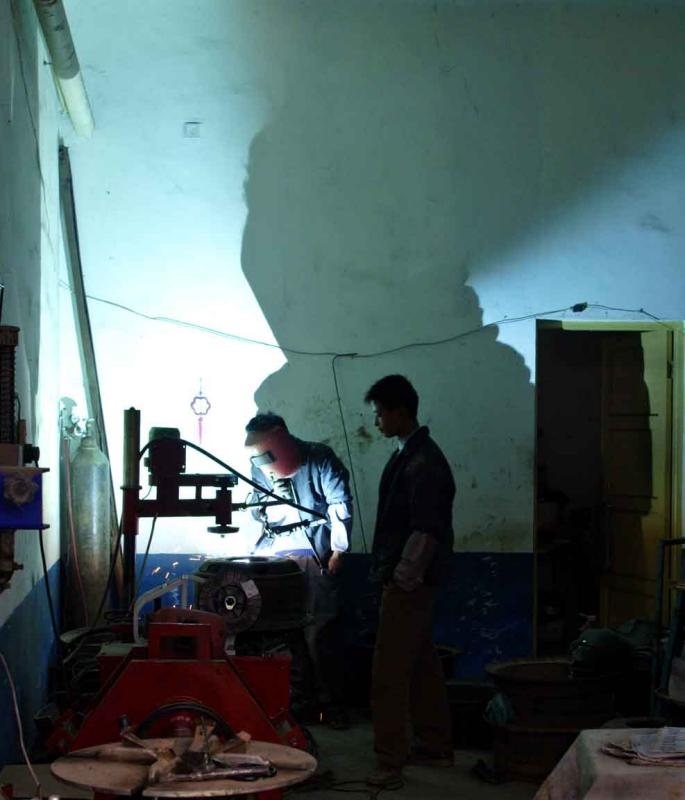 Arc welding while the helper is watching without eye protection. Jishou City, China.