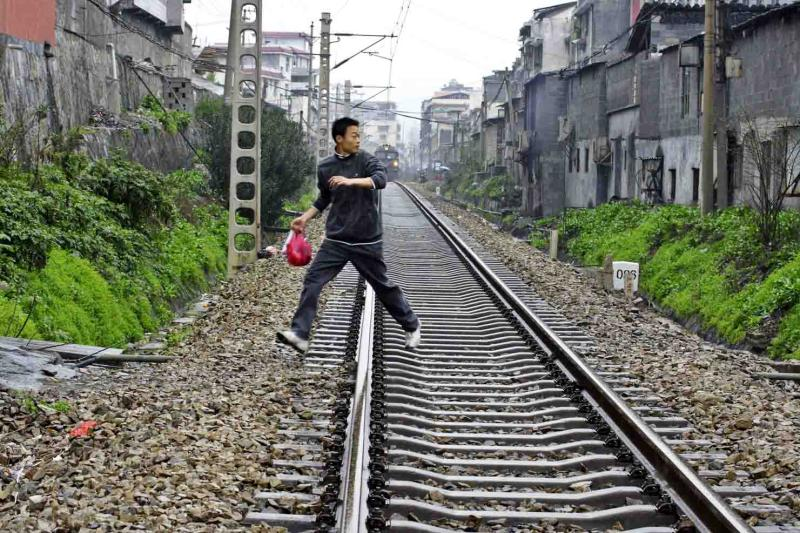Crossing the tracks with the train coming on fast.  Jishou City, China.