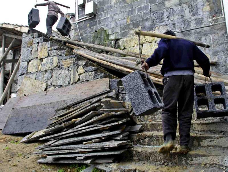 Hauling cement blocks. Jishou City, China.
