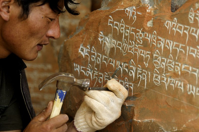 Carefully carving religious stones.