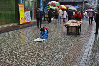 Begging, sidewalk wet and muddy.