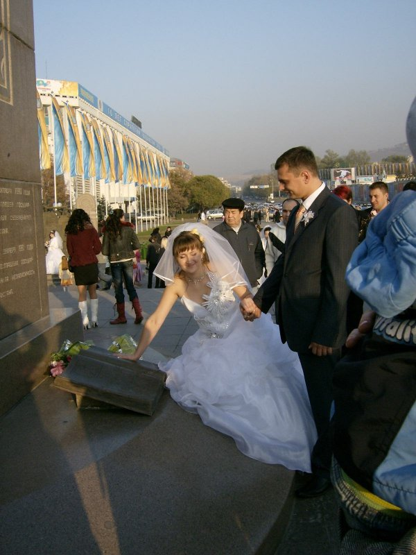 Bride places her hand into the Nazarbayev palm print in the Independence Book at the foot of the column