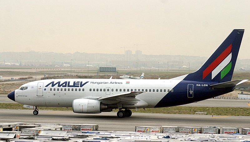 Malev 737-300 taxi past a sea of cargo containers