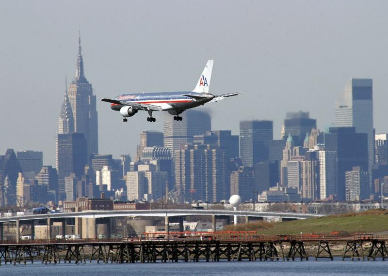 Ex-TWA 757 in AA color landing on LGA RWY 22, with NY skyline as the background