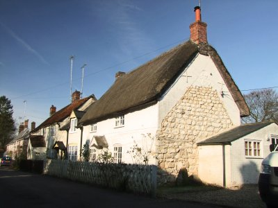 A  row  of  thatched  white  walled  cottages, some  without  thatches.