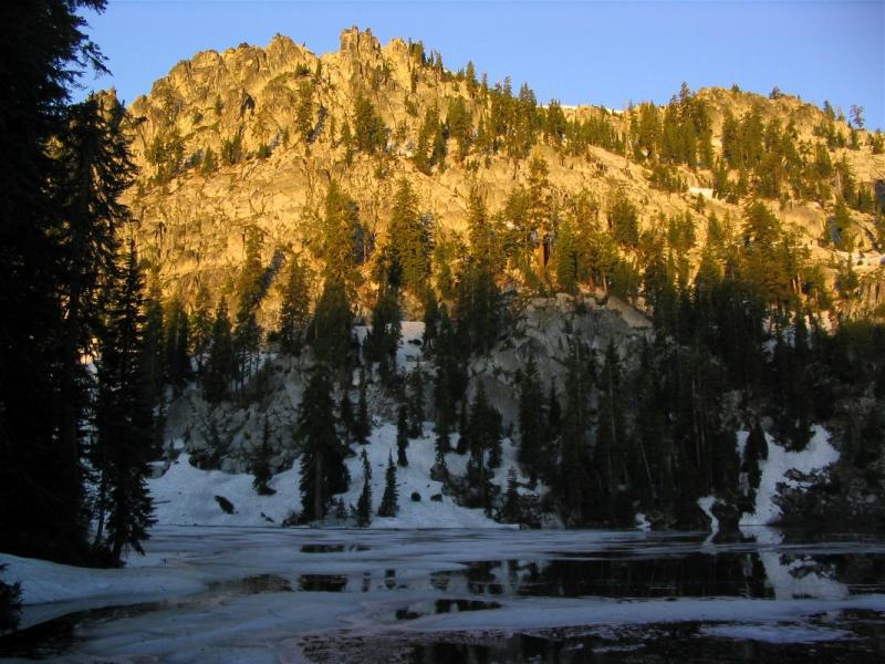 Doe Lakes sunrise glows on ice, snow, and rock in July