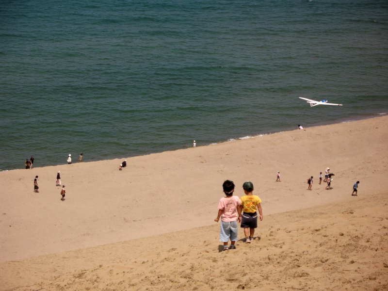 Young kids running down the sandy slope