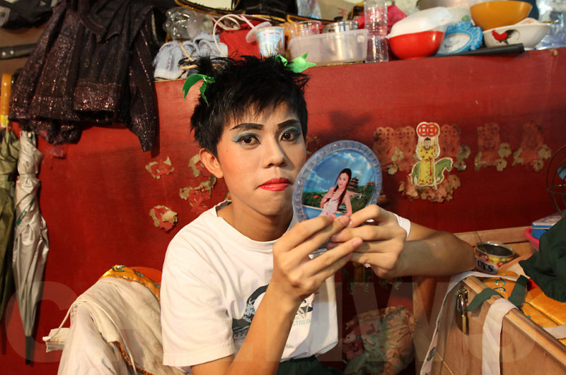 A young actor does his own make-up before the show.