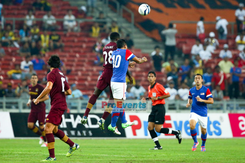 Kolo Toure (28) beats Mohd Safee (10) to the header