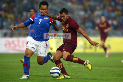 Carlos Tevez strikes as M. Aidil Zafuan (7) moves in