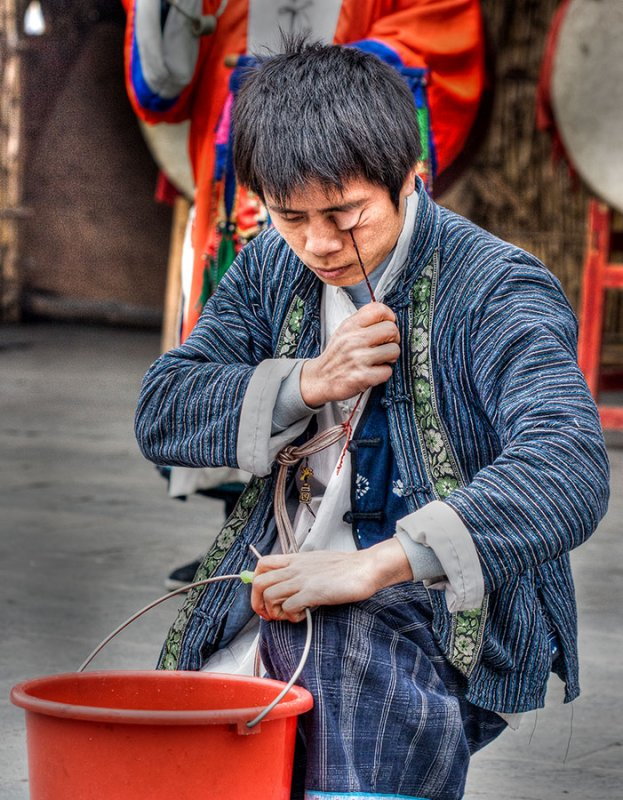 In a remote village, a kung fu performer prepares to pick up a bucket of water. IMG_0365_t2.jpg