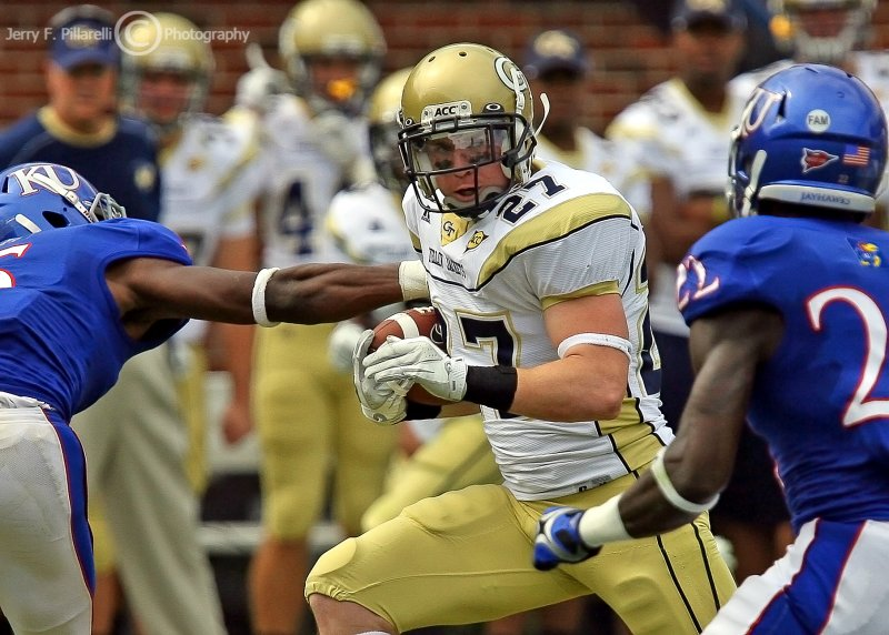 …Georgia Tech B-back Lyons picks his way through Kansas defenders for a big gain