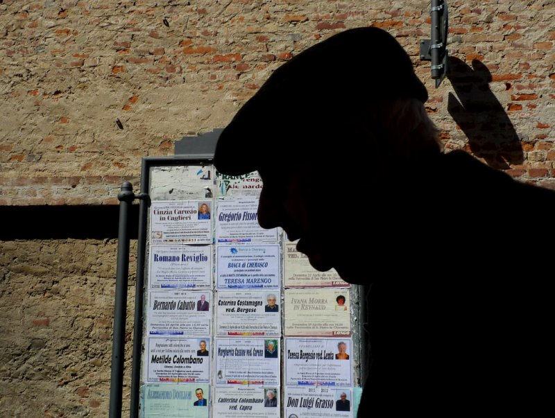 The last Contrast - A old man walk in front obituary notices of his fellow citizens