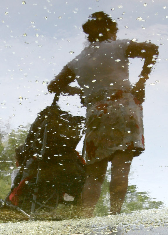Woman & Baby Stroller Reflected in a Puddle of Water