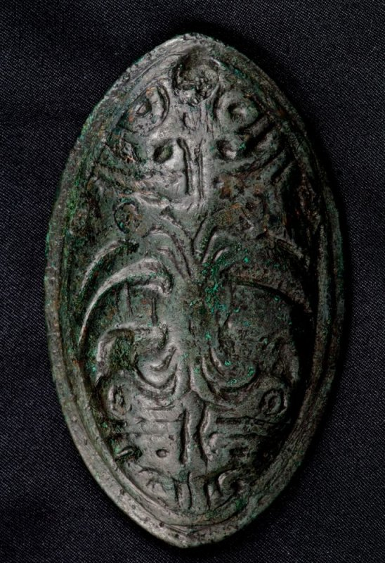 Two birds (ravens?) on 79 mm 10th Century cast bronze elliptical tortoise brooch, Alnwick, Northumbria, UK.